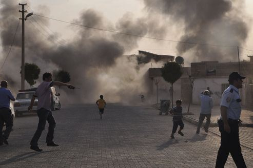 Smoke rises over the streets after an mortar bomb landed from Syria in the border village of Akcakale, southeastern Sanliurfa province