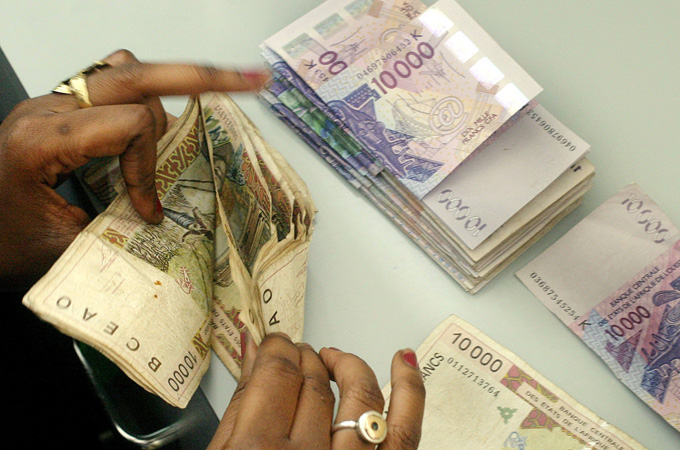 A Senegalese bank teller counts a pile of old 10 000 CFA Franc notes (Approximately 15 Euros) to be replaced with the new 10 000 CFA Franc notes seen above as part of a massive campaign