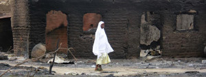 A woman walks past burnt houses in the aftermath of what Nigerian authorities said was heavy fighting between security forces and Islamist militants in Baga