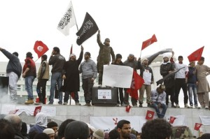 Salafist protesters wave flags during a protest in front of the Tunisian TV headquarters in Tunis