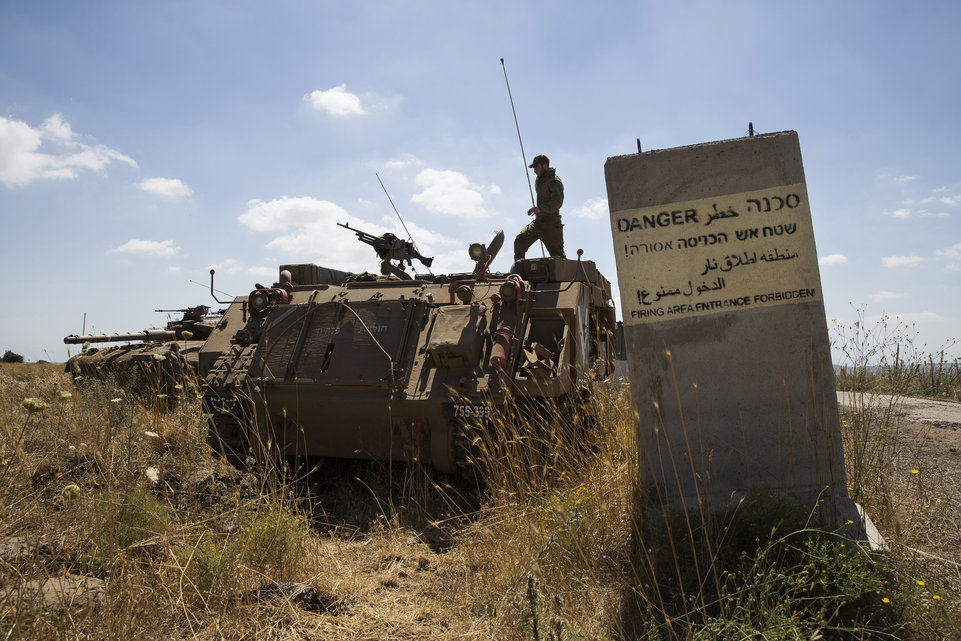 An Israeli soldier stands atop a tank near Alonei Habashan on the Israeli occupied Golan Heights