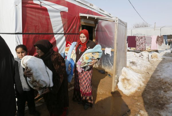 A Syrian refugee family carries 18-day-old triplets, whose mother died during childbirth in a nearby hospital, in a refugee camp near Zahle town in the Bekaa Valley